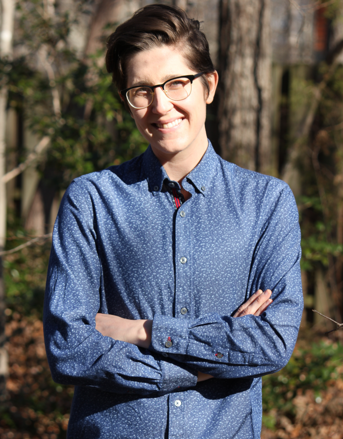A photo of Sarah Heying from the waist up. Standing outside in front of trees. Wearing glasses and a blue button-up shirt. Smiling, arms crossed.